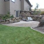 Transitional Patio with large landscape boulders lining patio